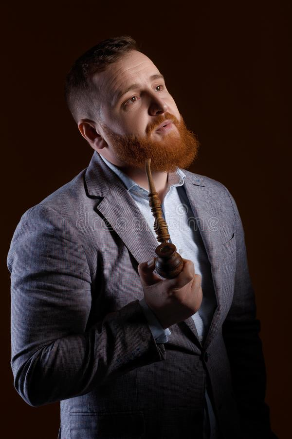 Man smoking a pipe. Portrait of a red bearded man smoking a pipe on a brown background stock photography