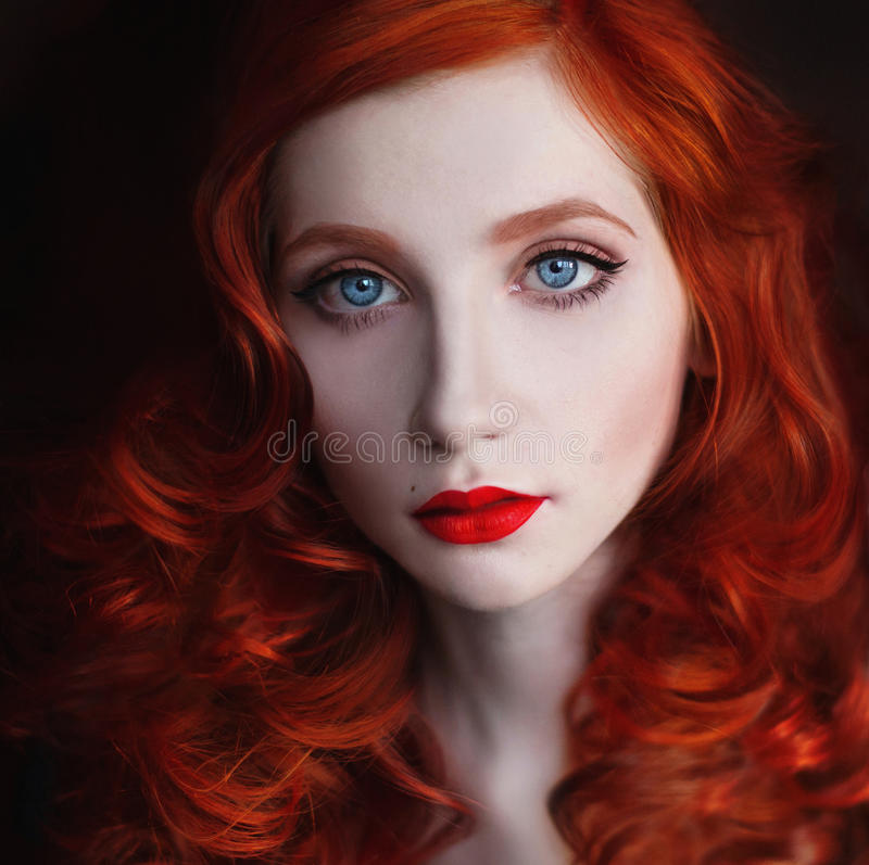 Portrait of red-haired girl with big blue eyes and red lips stock photos