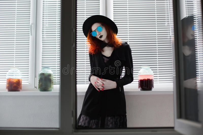 Portrait of red-haired girl in bow tie on a dark background, gothic style royalty free stock images