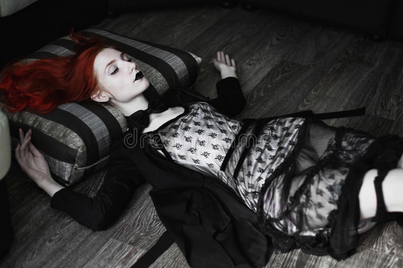 Portrait of red-haired girl in bow tie on a dark background, gothic style. Girl in a black dress, sense of fashion style, girl in dress and in a black cloak stock image