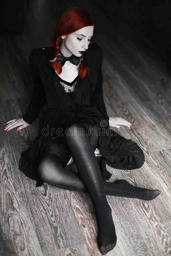 Portrait of red-haired girl in bow tie on a dark background, gothic style, stock image