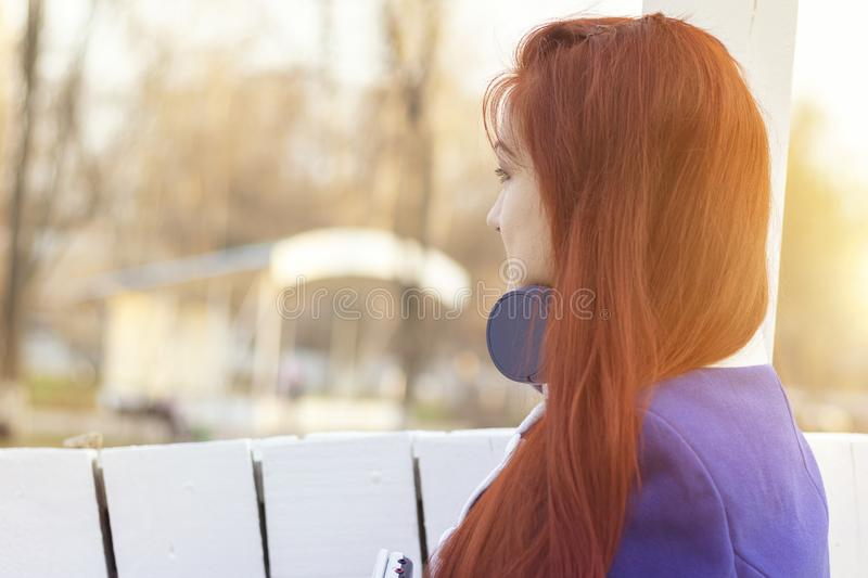 Portrait of a red-haired girl in a half-turn, face is not visible. A young woman with headphones in spring and autumn in the park stock images