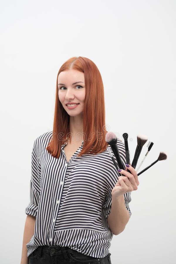 Portrait of a red-haired girl, make-up of actor, professional on white background. Paint brushes and palette in hand. stock photography