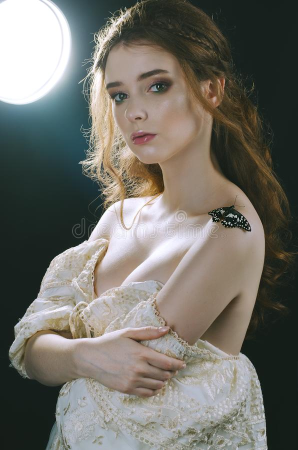 Portrait of a red-haired girl in a vintage gold dress with open shoulders, in backlight with a butterfly on her shoulder. Vintage. A princess. Fairy tale. Art stock image