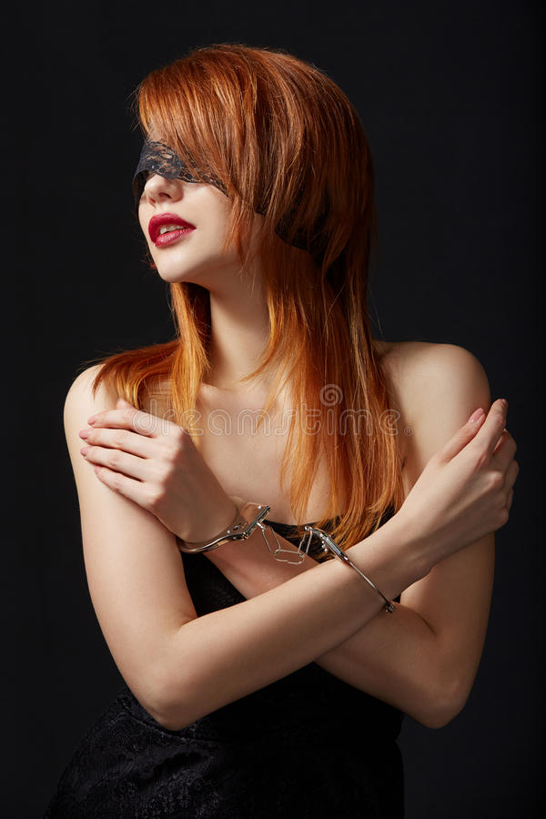 Portrait of red-haired submissive in handcuffs stock photography