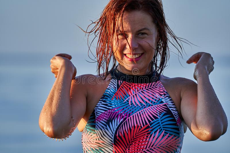 Portrait of a red-haired wet laughing woman of middle age in a swimsuit on a summer evening in the light of the setting sun. Close-up stock image