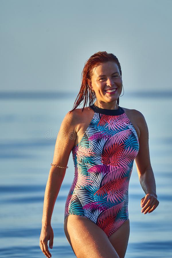 Portrait of a red-haired wet middle-aged woman in a swimsuit on a summer evening. In the light of the setting sun royalty free stock images