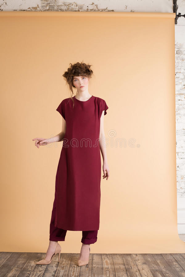 Portrait of red-haired woman with freckles in a burgundy dress on beige background. royalty free stock image
