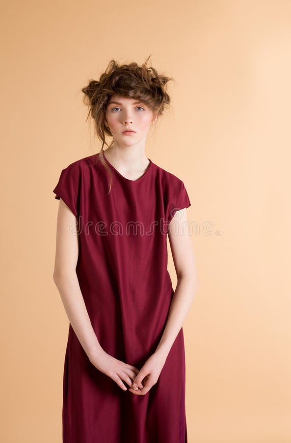 Portrait of red-haired woman with freckles in a burgundy dress on beige background. royalty free stock photography
