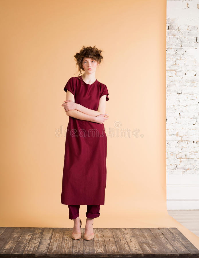 Portrait of red-haired woman with freckles in a burgundy dress on beige background. Fashion model. Woman with perfect skin. royalty free stock image