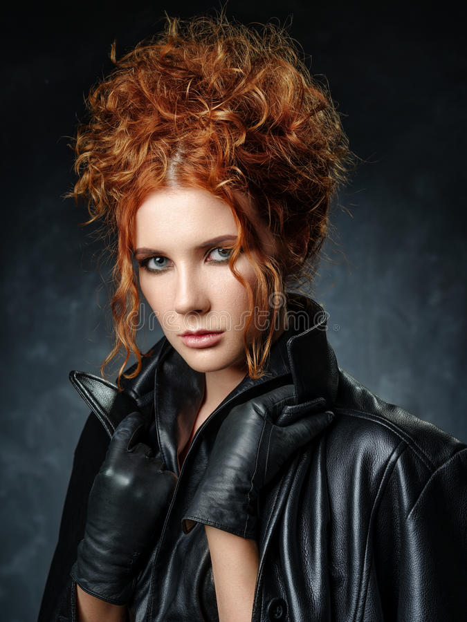 Portrait of red-haired woman in a leather jacket on a dark background. Seductive look at the camera stock photos