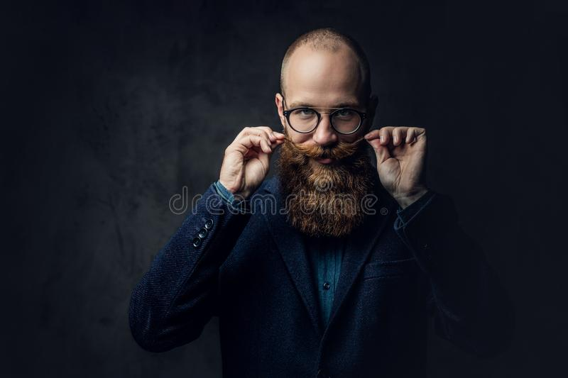 Redhead bearded male in a suit. Portrait of redhead bearded male in eyeglasses dressed in an elegant wool suit over grey background royalty free stock photo