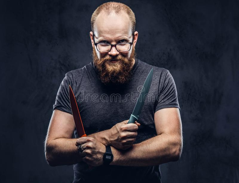 Portrait of a redhead bearded male wearing glasses dressed in a gray t-shirt, standing with colored steel knives in his. Hands. Isolated on dark textured stock photos