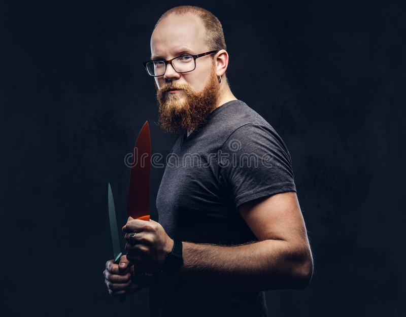 Portrait of a redhead bearded male wearing glasses dressed in a gray t-shirt, standing with colored steel knives in his. Hands. Isolated on dark textured stock images