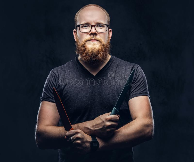 Portrait of a redhead bearded male wearing glasses dressed in a gray t-shirt, standing with colored steel knives in his. Hands. Isolated on dark textured stock photography