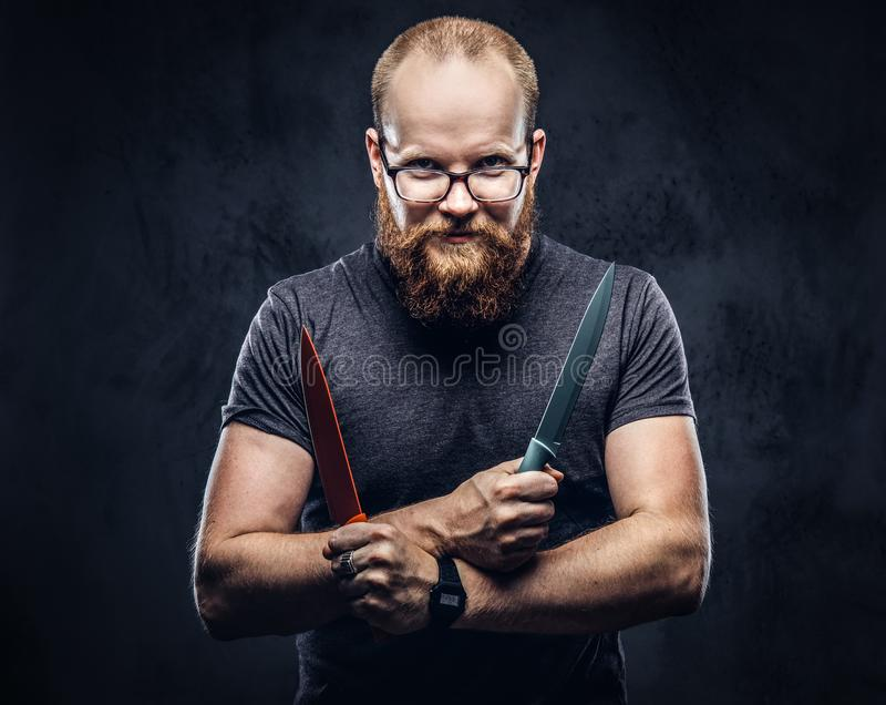 Portrait of a redhead bearded male wearing glasses dressed in a gray t-shirt, standing with colored steel knives in his. Hands. Isolated on dark textured stock photo