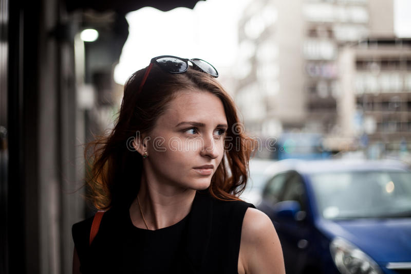 Portrait of a redhead business woman looking for something in a street od Belgrade, Serbia stock image