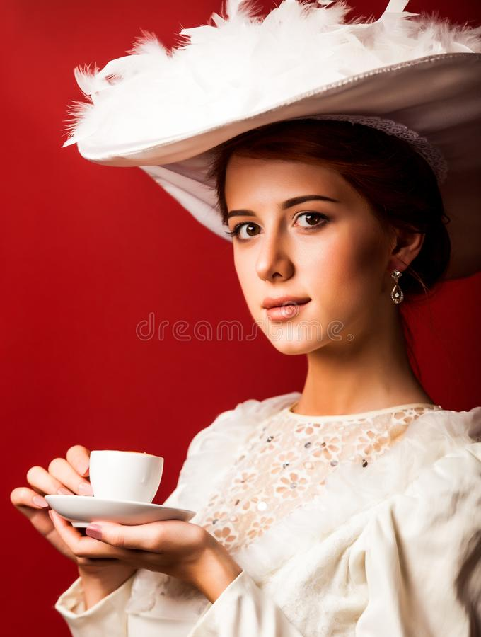 Portrait of redhead edvardian woman with cup. On red background stock images