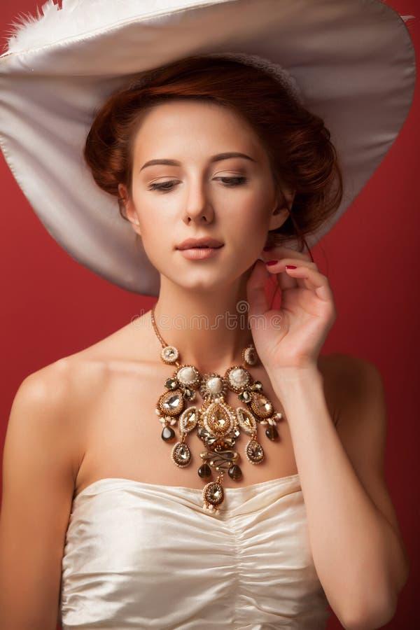 Portrait of redhead edwardian women. Portrait of redhead edwardian woman with necklace on red background royalty free stock photo
