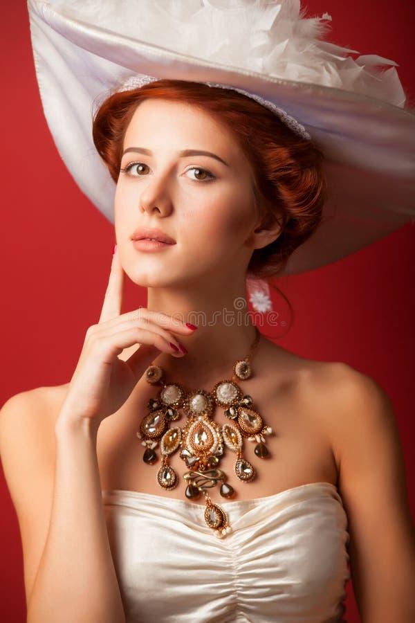 Portrait of redhead edwardian women. Portrait of redhead edwardian woman with necklace on red background royalty free stock photography