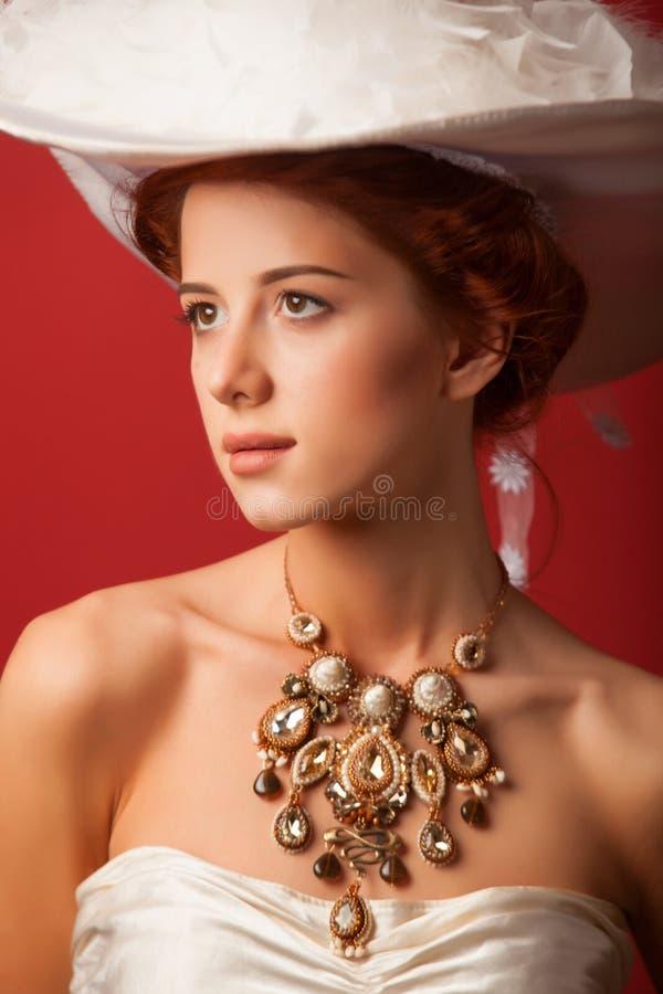Portrait of redhead edwardian women. Portrait of redhead edwardian woman with necklace on red background stock photos
