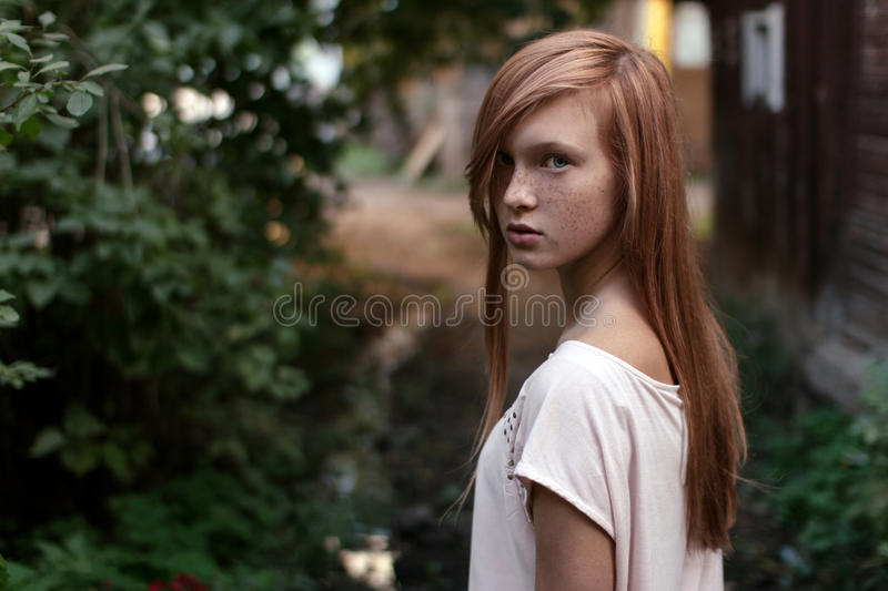 Portrait of a redhead girl with freckles and blue eyes standing in half-turn in the green garden looking at camera royalty free stock photo