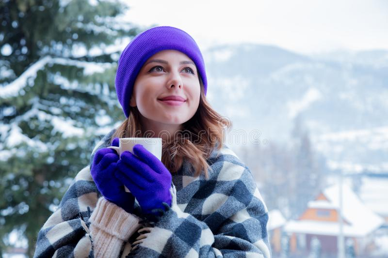 Portrait of redhead girl in plaid and purple hat with cup. Of hot drink at winter outdoor stock photos