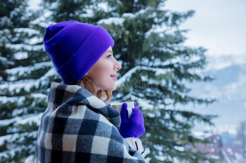 Portrait of redhead girl in plaid and purple hat with cup. Of hot drink at winter outdoor royalty free stock images