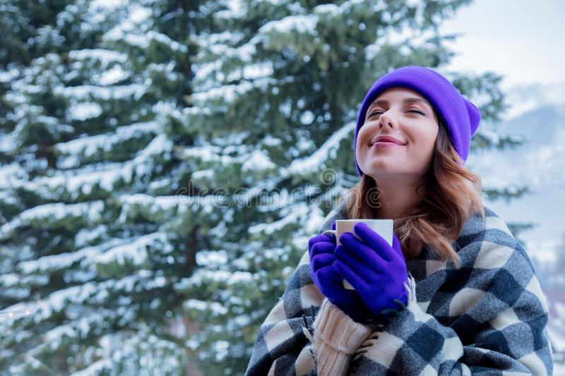 Portrait of redhead girl in plaid and purple hat with cup. Of hot drink at winter outdoor stock photo