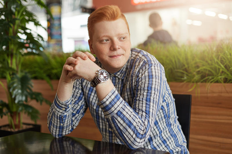 A portrait of redhead man with freckles wearing stylish checked shirt and watch sitting in cosy cafe waiting for his friends to co royalty free stock photography