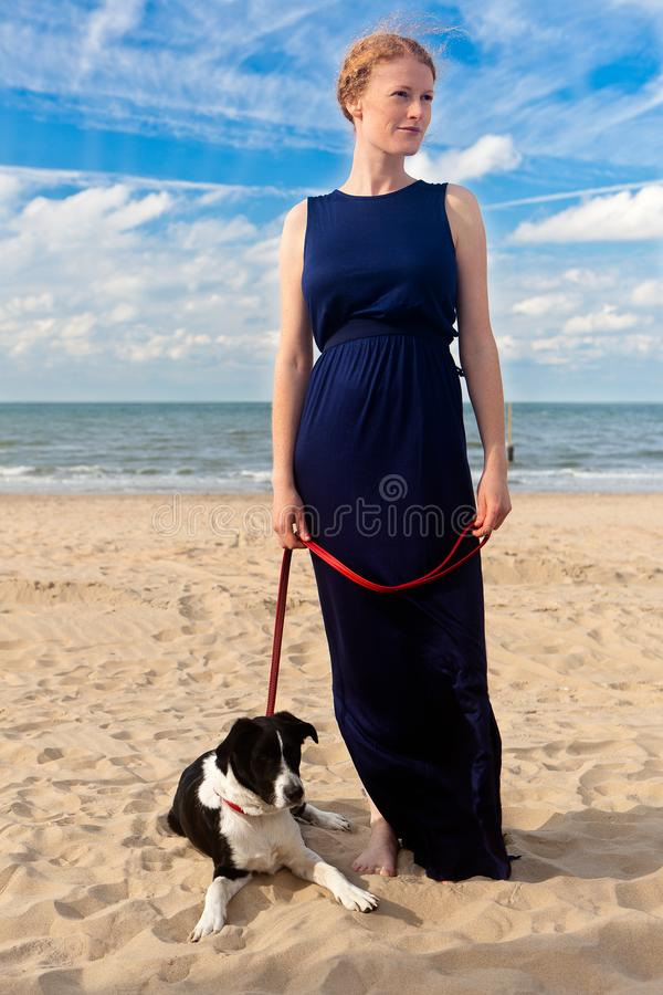 Redhead woman dog beach, De Panne, Belgium. Portrait of a redhead woman in a blue dress and her black and white dog at the leading string on the beach with the stock photo