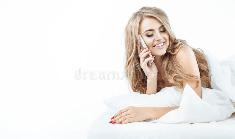Portrait of a relaxed blonde using a smartphone stock photography