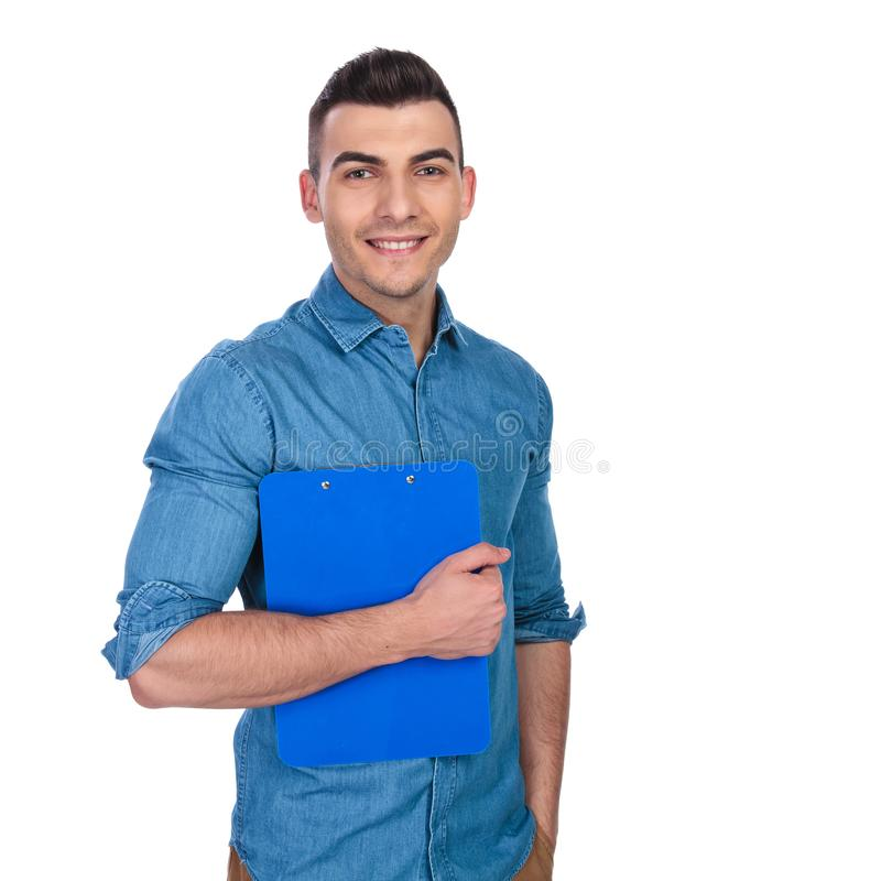 Portrait of relaxed casual man holding blue clipboard stock image