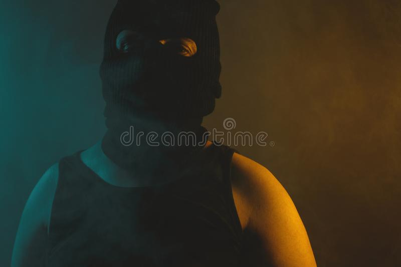 Portrait of relaxed man in black balaclava, illuminated from abstract light in green and yellow colors stock images