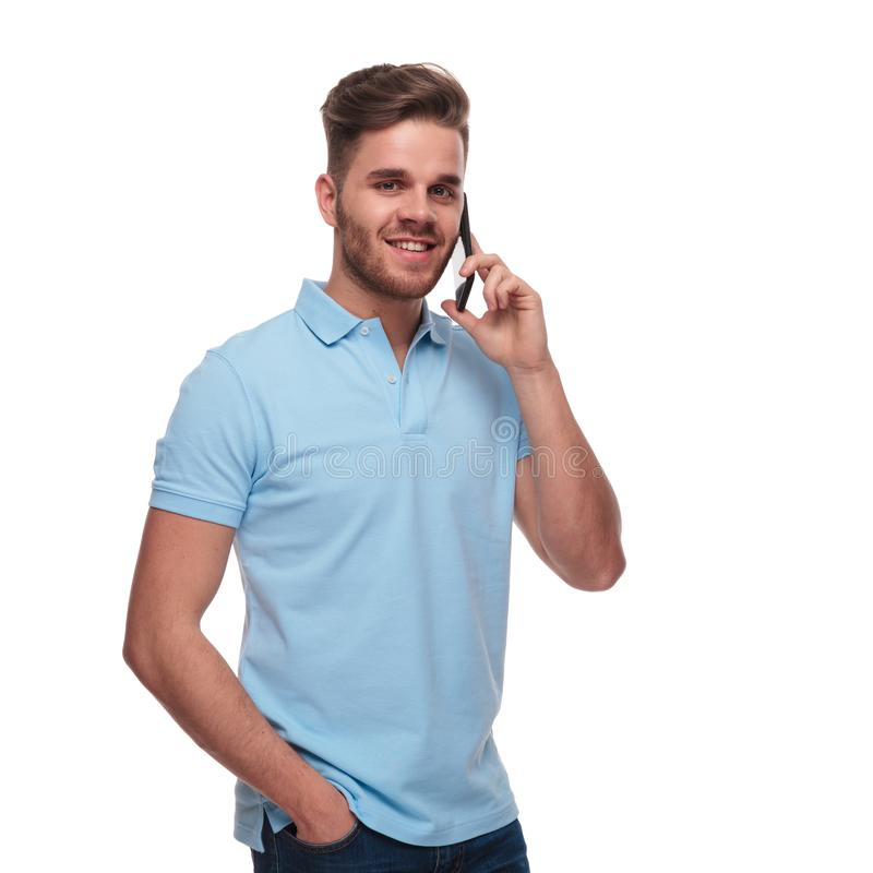 Portrait of relaxed man in polo shirt speaking on phone. Portrait of relaxed man in polo shirt speaking on the phone while standing on white background with a stock photos