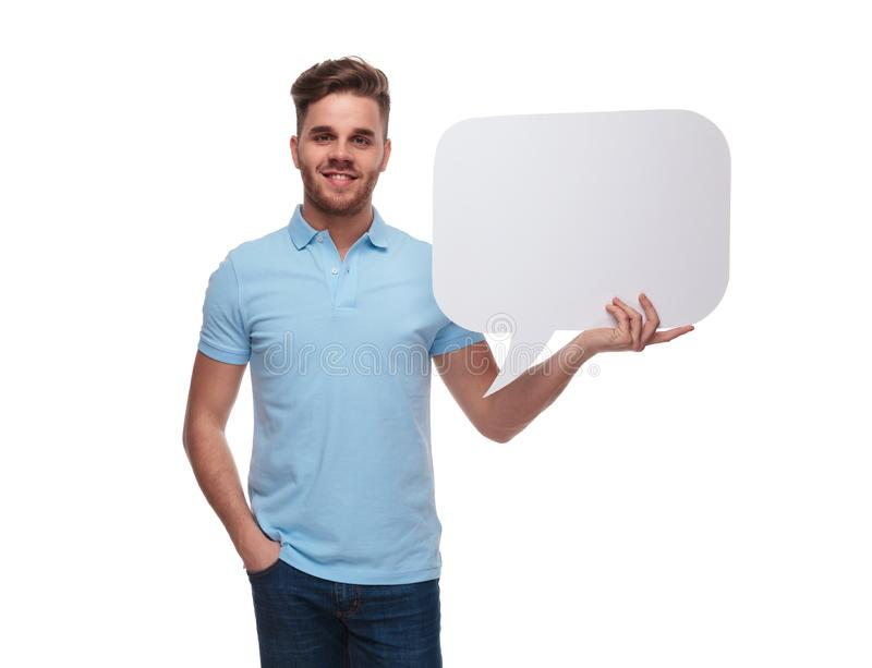 Portrait of relaxed man wearing polo shirt holding speech bubble. Portrait of relaxed man wearing blue polo shirt holding speech bubble while standing on white royalty free stock image