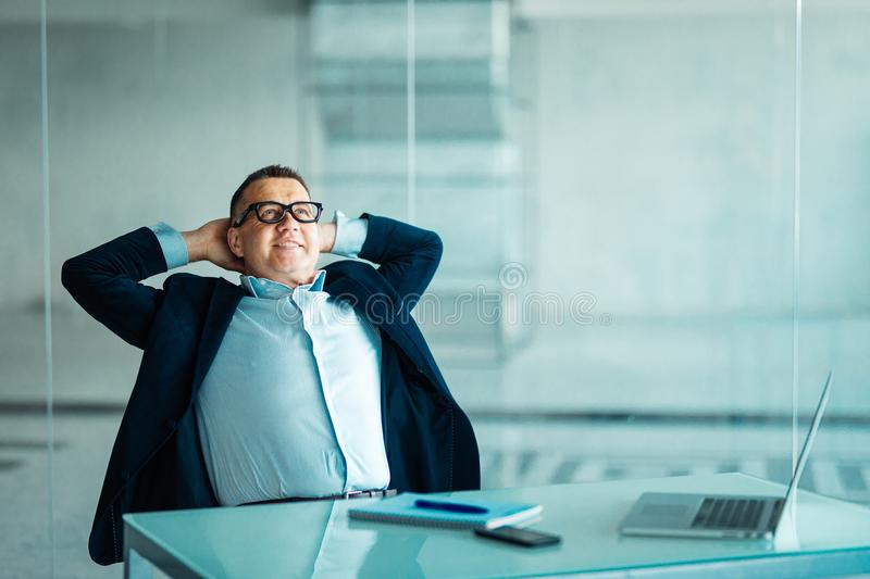 Portrait of relaxed senior manager sitting at office and leaning back. royalty free stock photography