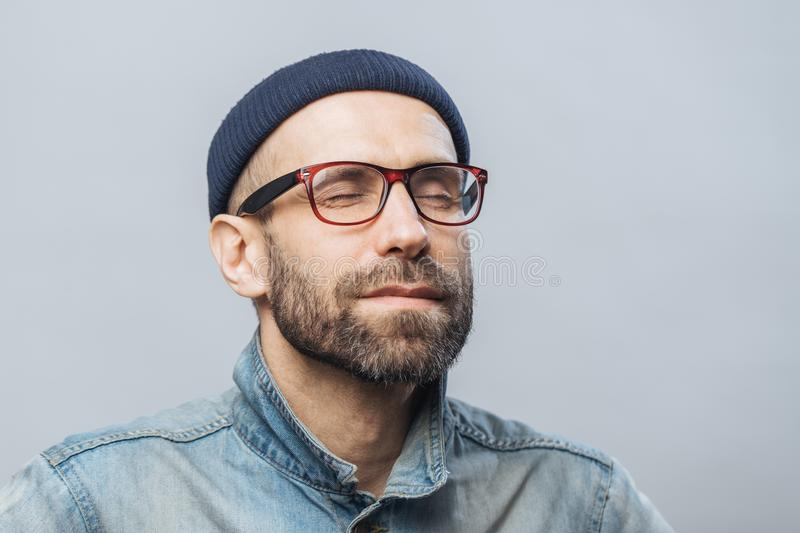 Portrait of relaxed unshaven male with closed eyes wears glasses, keeps eyes closed, enjoys calm atmosphere, isolated over white b. Ackground. People, relaxation stock images