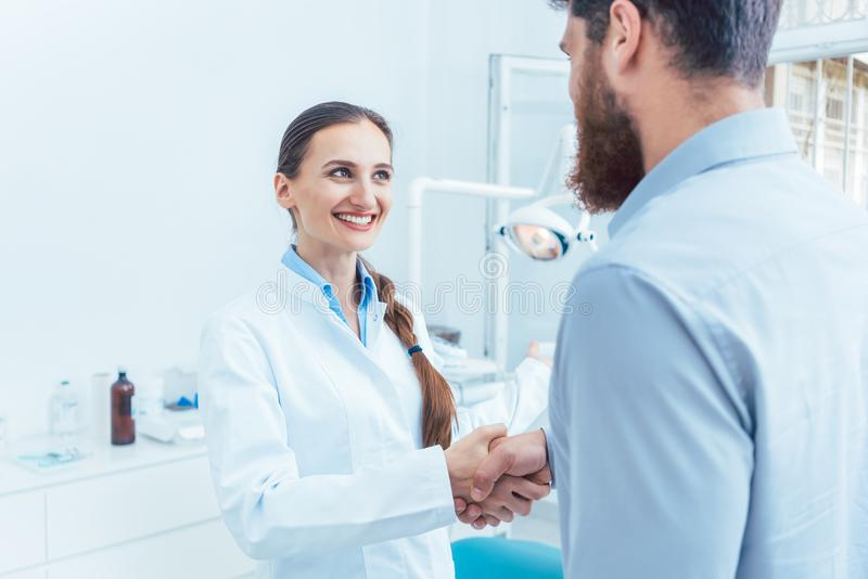 Portrait of a reliable and cheerful dentist shaking the hand of a patient stock images