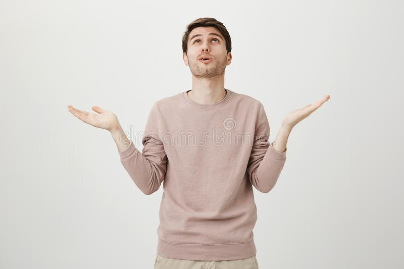 Portrait of relieved handsome young man with cute haircut looking up with raised palms as if saying God why me, standing. Against gray background. Guy was royalty free stock photo