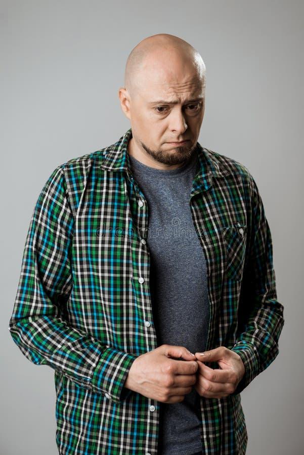 Portrait of resentful sad emotive man over beige background. stock images