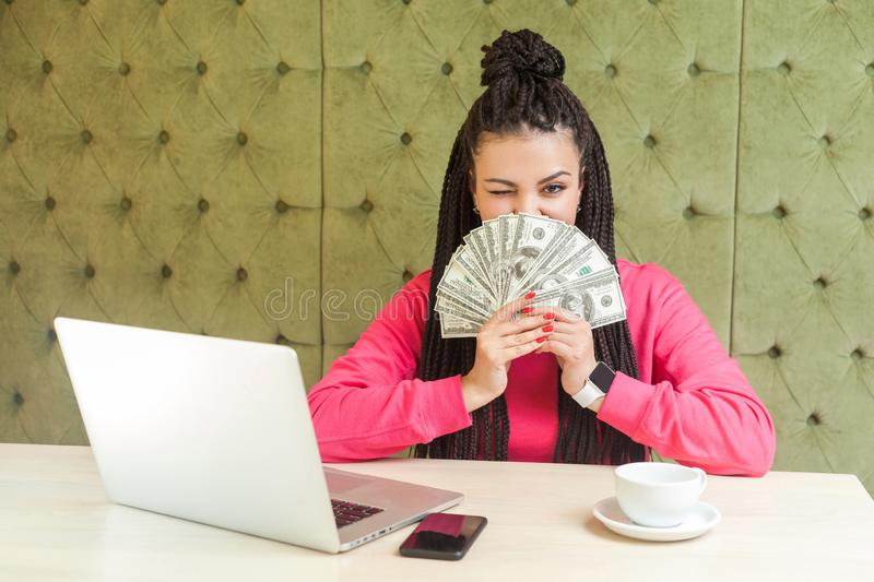 Portrait of rich attractive young adult businesswoman with black dreadlocks hairstyle in pink blouse is sitting and showing fan of stock images