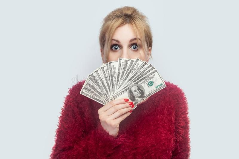 Portrait of rich attractive young adult businesswoman in red blouse standing and showing fan of cash dollars with big crazy eyes royalty free stock images