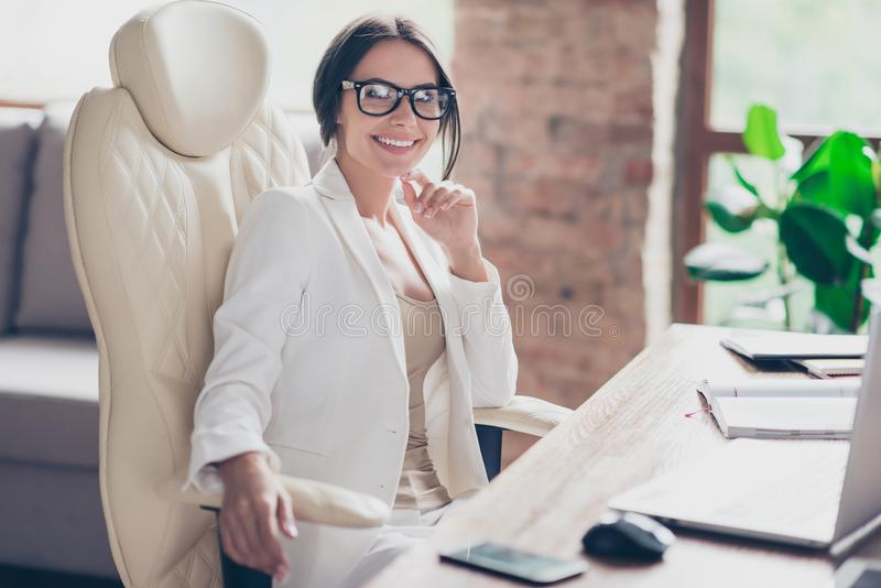 Portrait of rich famous successful confident smiling professional attractive business lady sitting at the desktop in contemporary stock photo