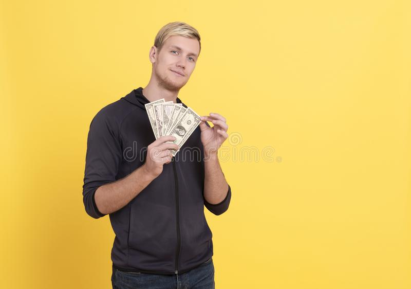 Portrait of rich man holding dollar money isolated over yellow background.  royalty free stock photography