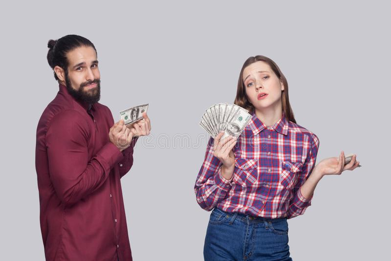 Portrait of rich serious woman with fan of money and near sad poor man, standing and looking at camera stock photos