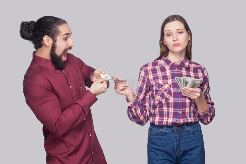 Portrait of rich serious woman with fan of money, sharing with amazed or surprised hungry man. standing and looking at camera like stock photography