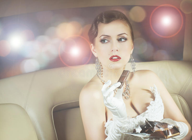 Portrait of a rich woman eating chocolate in a car. Young and beautiful celebrity woman sitting in a luxury car and eating a chocolate royalty free stock photos