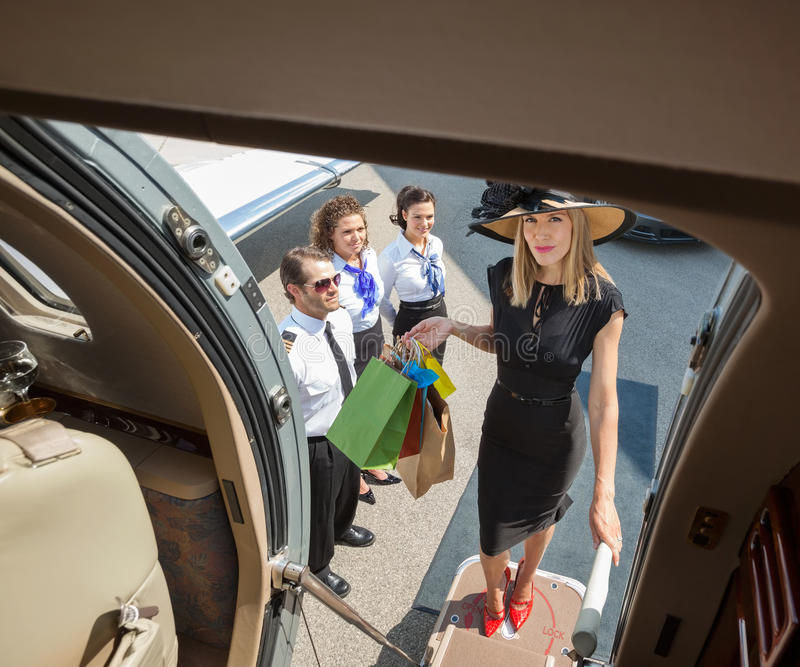 Portrait Of Rich Woman With Shopping Bags Boarding