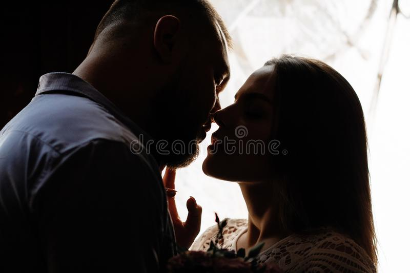 Portrait of a romantic couple in a backlight from a window or door, silhouette of a couple in a doorway with a backlight, couple o royalty free stock image